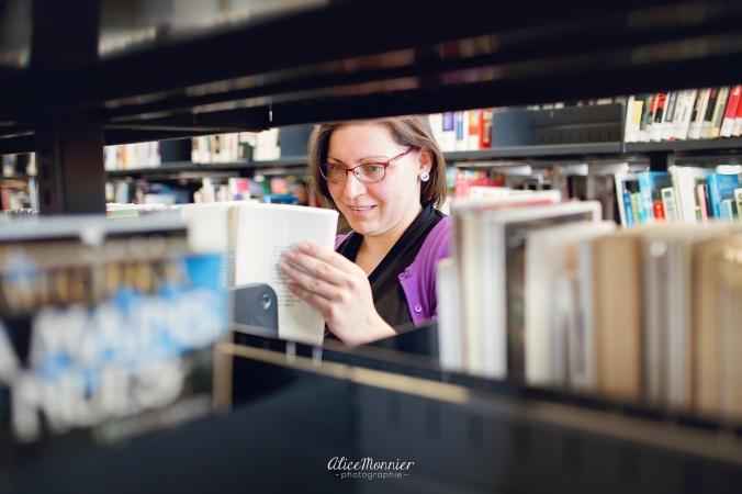 Julie fouille dans les rayons à la bibliothèque.