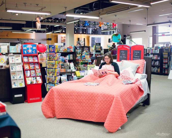 Julie lit au lit, dans un lit dans une librairie.