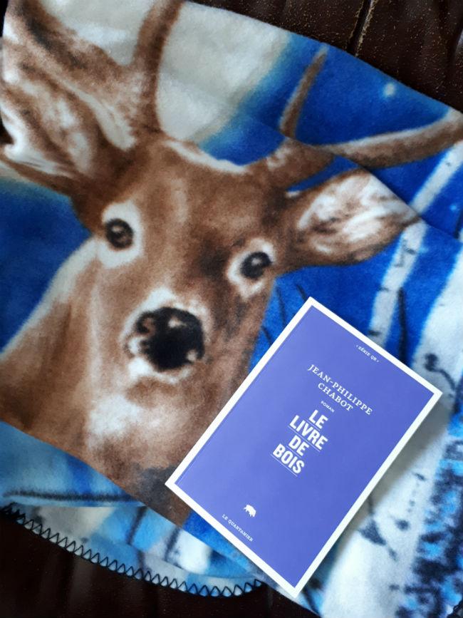 """Le roman """"Le livre de bois"""" accompagné d'un animal de bois, avec bois."""